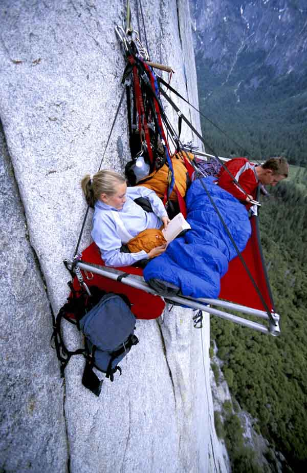 man and woman rock climbing / resting on porta-ledge on the side of El Capitan  in Yosemite National Park, California.